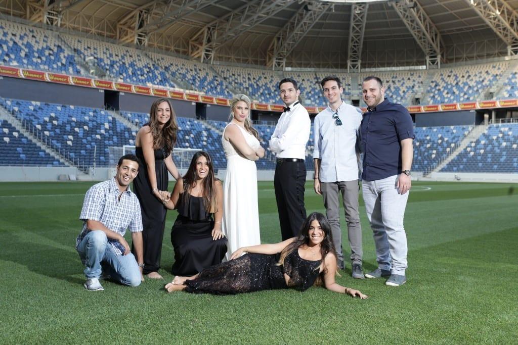 צילומי טרום חתונה, זוג וחברים מלווים, על כר הדשא באצטדיון