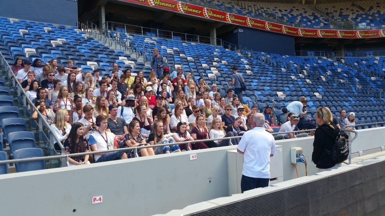 קבוצת תיירים ביציעי האצטדיון במהלך סיור מודרך